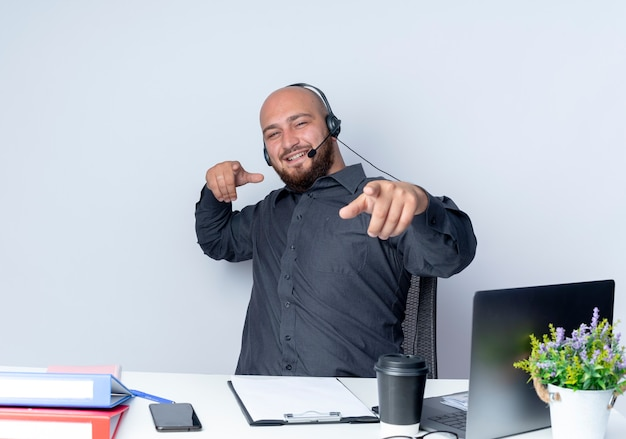 Lächelnder junger kahler callcenter-mann, der headset trägt, das am schreibtisch mit arbeitswerkzeugen sitzt, die sie geste an der front lokalisiert auf weißer wand tun