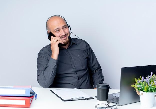 Lächelnder junger kahler callcenter-mann, der headset trägt, sitzt am schreibtisch mit arbeitswerkzeugen, die zur seite schauen und am telefon lokalisiert auf weißer wand sprechen