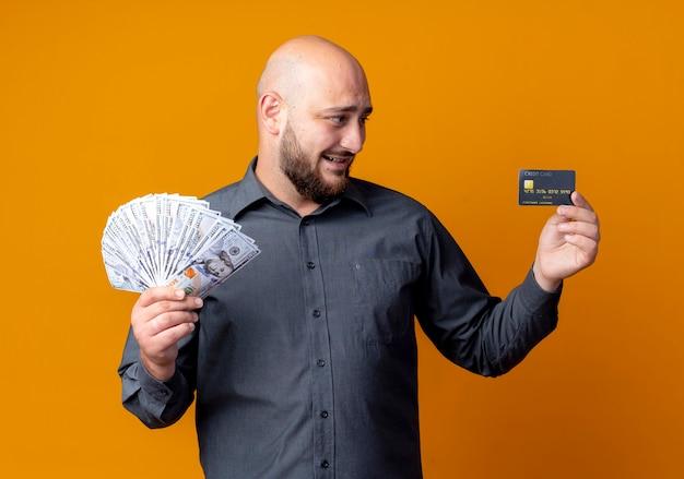 Lächelnder junger kahler callcenter-mann, der kreditkarte und geld hält und karte lokalisiert auf orange wand betrachtet