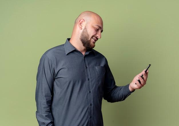 Lächelnder junger kahlköpfiger callcenter-mann, der handy lokalisiert auf olivgrüne wand hält und betrachtet