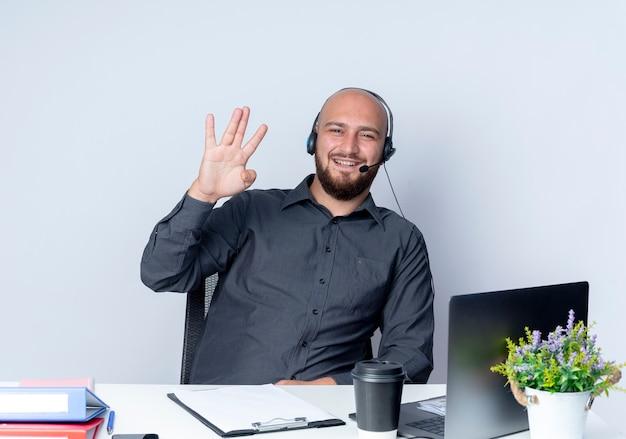 Lächelnder junger kahlköpfiger callcenter-mann, der headset trägt, das am schreibtisch mit arbeitswerkzeugen sitzt, die vier mit der hand lokalisiert auf weißer wand zeigen