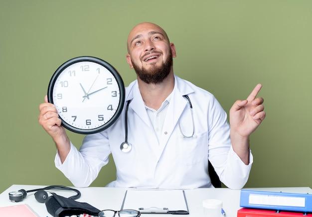 Lächelnder junger kahlköpfiger männlicher arzt, der medizinische robe und stethoskop trägt, die an der schreibtischarbeit sitzen