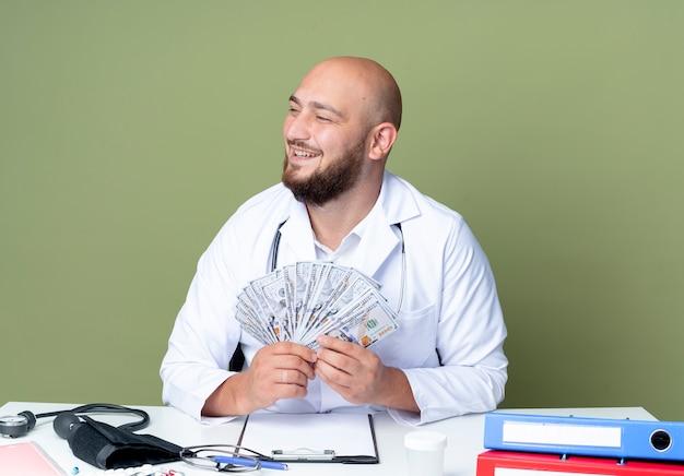 Lächelnder junger kahlköpfiger männlicher arzt, der medizinische robe und stethoskop trägt, die an schreibtischarbeit mit medizinischen werkzeugen sitzen, die bargeld lokalisiert auf grünem hintergrund halten