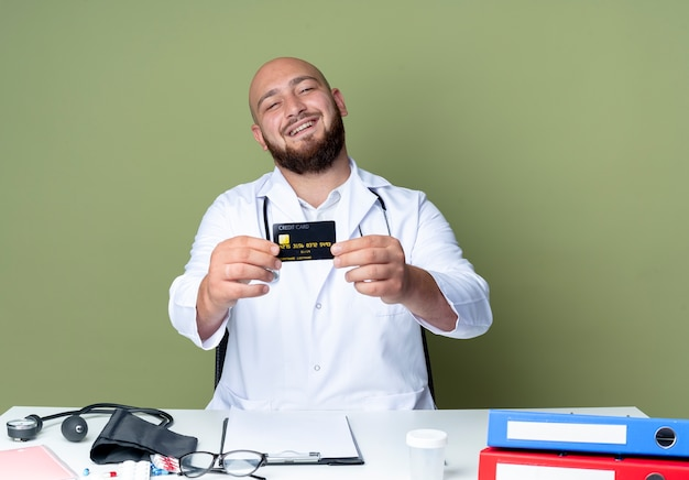 Lächelnder junger kahlköpfiger männlicher arzt mit medizinischem gewand und stethoskop am schreibtisch sitzend
