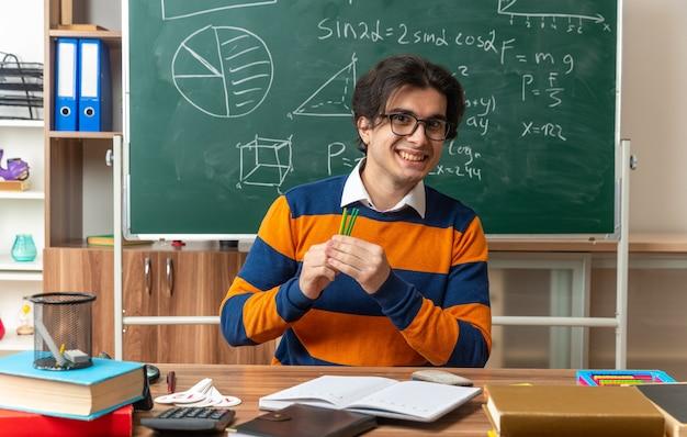 Lächelnder junger kaukasischer geometrielehrer mit brille, der am schreibtisch mit schulmaterial im klassenzimmer sitzt und zählstäbe hält, die nach vorne schauen