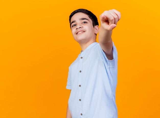 Lächelnder junger kaukasischer junge, der auf kamera lokalisiert auf orange hintergrund mit kopienraum schaut und zeigt