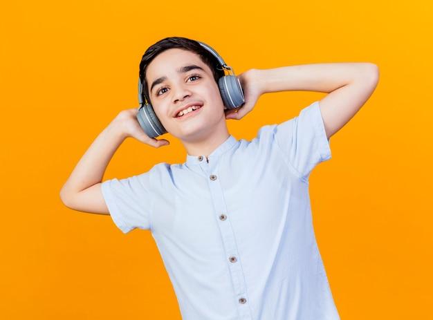 Lächelnder junger kaukasischer junge, der kopfhörer trägt, die sie betrachten kamera lokalisiert auf orange hintergrund