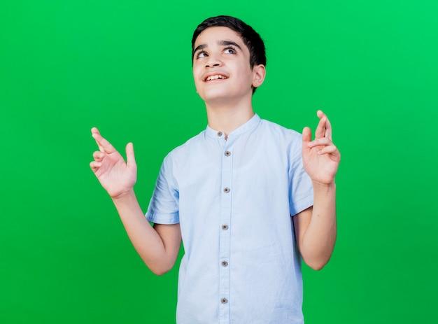 Lächelnder junger kaukasischer junge, der seitenkreuzungsfinger betrachtet, die auf der grünen wand lokalisiertes glück wünschen