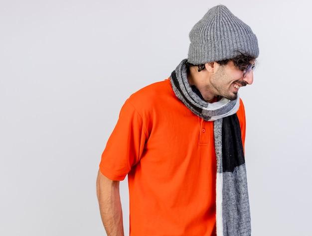 Lächelnder junger kaukasischer kranker mann, der brille wintermütze und schal trägt kopf zu seite mit geschlossenen augen, die auf weißem hintergrund mit kopienraum isoliert werden