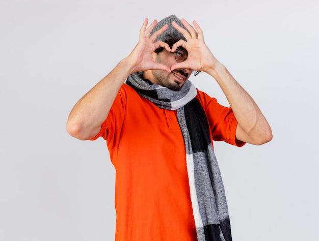 Lächelnder junger kaukasischer kranker mann, der brille wintermütze und schal tut, die herzzeichen betrachten kamera lokalisiert auf weißem hintergrund tun