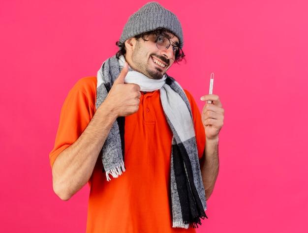 Lächelnder junger kaukasischer kranker mann, der brillenwintermütze und -schal betrachtet, die kamera hält, die thermometer hält daumen oben auf purpurrotem hintergrund mit kopienraum zeigt