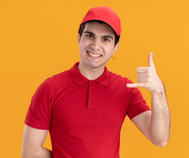 Lächelnder junger kaukasischer lieferbote in blauer uniform und mütze, die die hand hinter dem rücken hält und eine lockere geste macht