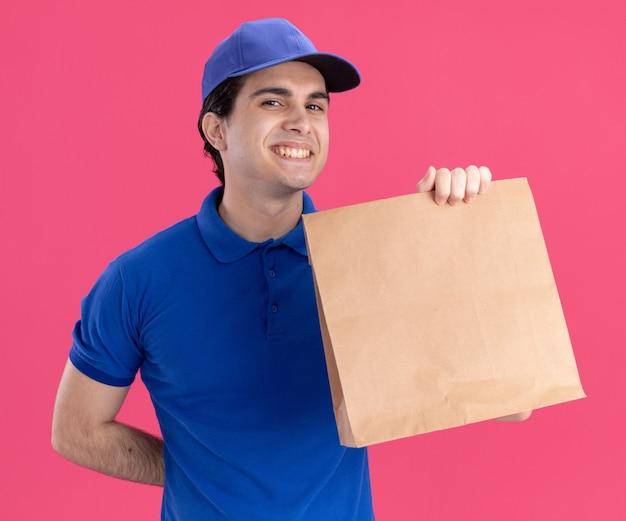 Lächelnder junger kaukasischer lieferbote in blauer uniform und mütze mit papierpaket, das die hand hinter dem rücken hält, isoliert auf rosa wand