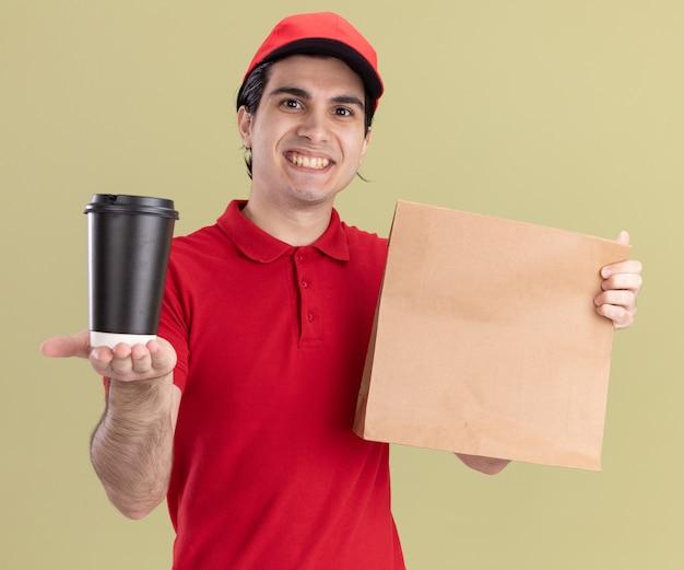 Lächelnder junger kaukasischer lieferbote in roter uniform und mütze, der ein papierpaket hält und eine plastikkaffeetasse in richtung kamera ausstreckt und auf die kamera schaut, die auf olivgrünem hintergrund isoliert ist
