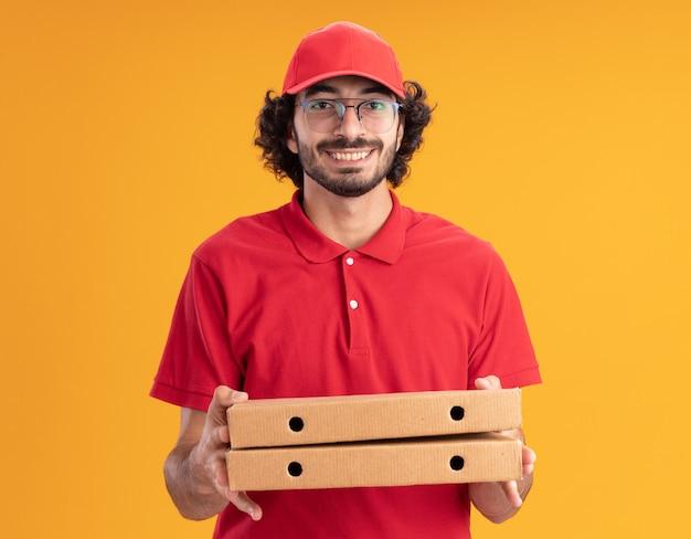 Lächelnder junger kaukasischer lieferbote in roter uniform und mütze mit brille, die pizzapakete isoliert auf oranger wand hält