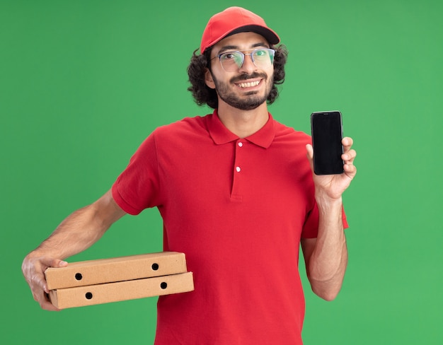 Lächelnder junger kaukasischer lieferbote in roter uniform und mütze mit brille, die pizzapakete mit handy hält