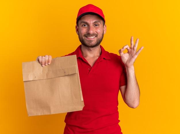 Lächelnder junger kaukasischer lieferbote in roter uniform und mütze mit papierpaket, das auf die kamera schaut und das ok-zeichen auf oranger wand isoliert tut