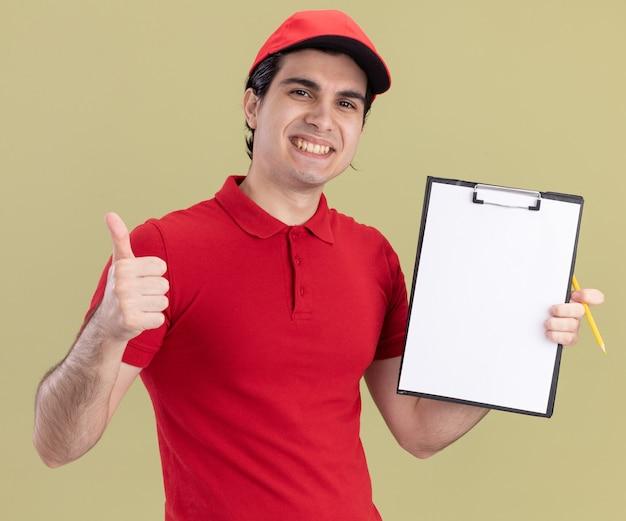 Lächelnder junger kaukasischer lieferbote in roter uniform und mütze mit zwischenablage, die daumen mit bleistift in einer anderen hand zeigt, isoliert auf olivgrüner wand