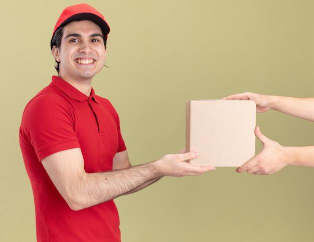 Lächelnder junger kaukasischer lieferbote in roter uniform und mütze