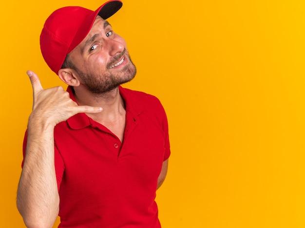 Lächelnder junger kaukasischer liefermann in roter uniform und mütze, der die hand hinter dem rücken hält und auf die kamera schaut, die anrufgeste einzeln auf orangefarbener wand mit kopierraum macht