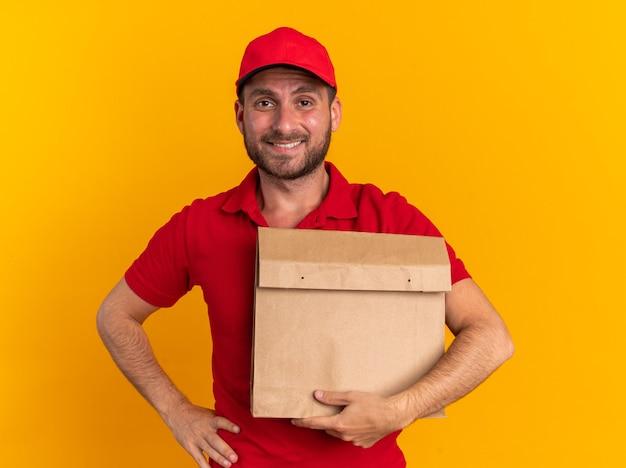 Lächelnder junger kaukasischer liefermann in roter uniform und mütze, der ein papierpaket hält, das die hand auf der taille hält und die kamera isoliert auf der orangefarbenen wand betrachtet