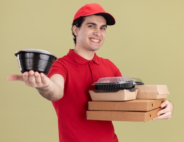 Lächelnder junger kaukasischer liefermann in roter uniform und mütze, der pizzapakete mit papiernahrungspaketen auf ihnen hält, die den lebensmittelbehälter einzeln auf olivgrüner wand ausstrecken?