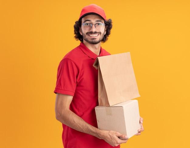 Lächelnder junger kaukasischer liefermann in roter uniform und mütze mit brille, der in der profilansicht steht und karton mit papierpaket darauf hält, der nach vorne schaut