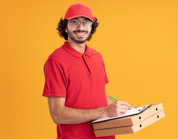 Lächelnder junger kaukasischer liefermann in roter uniform und mütze mit brille, der in der profilansicht steht und pizzapakete mit zwischenablage und bleistift nach vorne hält