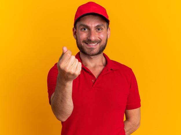 Lächelnder junger kaukasischer liefermann in uniform und mütze, der die hand hinter dem rücken hält und geldgeste macht