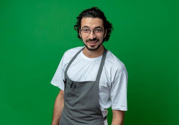 Lächelnder junger kaukasischer männlicher friseur, der brille und gewelltes haarband im einheitlichen stehen trägt und kamera lokalisiert auf grünem hintergrund mit kopienraum betrachtet