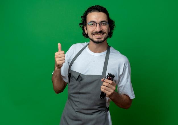 Lächelnder junger kaukasischer männlicher friseur, der brille und welliges haarband in uniform hält, die haarschneidemaschinen hält und daumen oben auf grünem hintergrund mit kopienraum zeigt