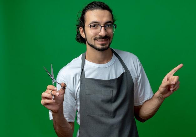Lächelnder junger kaukasischer männlicher friseur, der uniform und brille trägt, die schere hält und auf seite lokalisiert auf grünem hintergrund zeigt