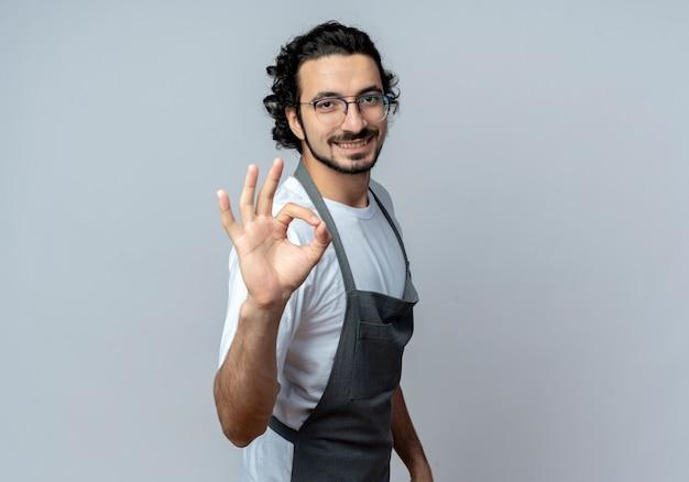 Lächelnder junger kaukasischer männlicher friseur mit brille und gewelltem haarband in uniform, der in der profilansicht steht und ein gutes zeichen macht