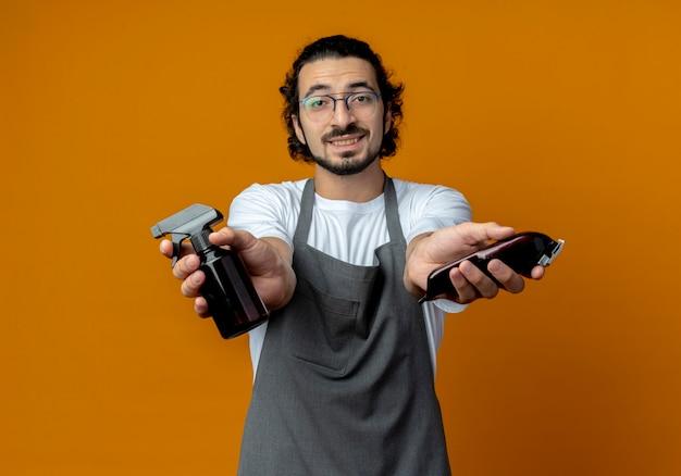 Lächelnder junger kaukasischer männlicher friseur mit brille und welligem haarband in uniform, das sprühflasche und haarschneidemaschinen ausstreckt