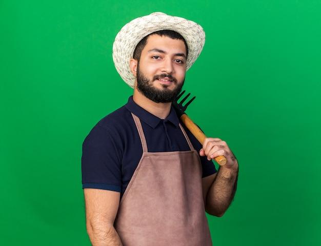 Lächelnder junger kaukasischer männlicher gärtner, der gartenhut hält, der rechen auf schulter lokalisiert auf grüner wand mit kopienraum hält