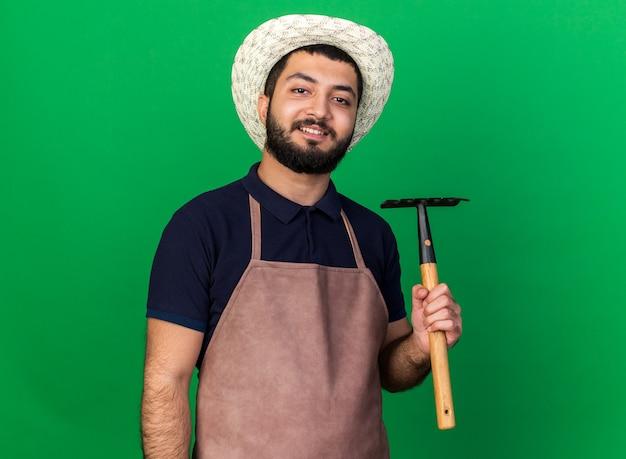 Lächelnder junger kaukasischer männlicher gärtner, der gartenhut hält, der rechen lokalisiert auf grüner wand mit kopienraum hält