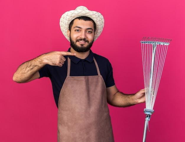 Lächelnder junger kaukasischer männlicher gärtner, der gartenhut hält und auf blattrechen lokalisiert auf rosa wand mit kopienraum zeigt