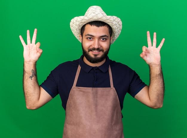 Lächelnder junger kaukasischer männlicher gärtner mit gartenhut, der ein ok-zeichen auf grüner wand mit kopienraum gestikuliert