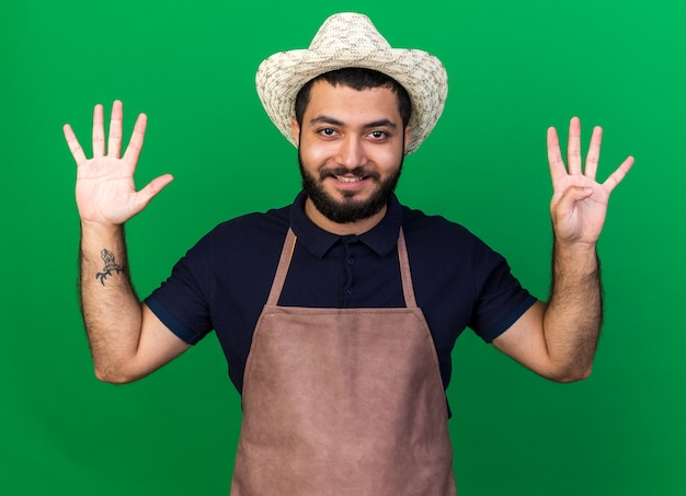 Lächelnder junger kaukasischer männlicher gärtner mit gartenhut, der neun mit fingern gestikuliert, die auf grüner wand mit kopienraum isoliert sind?