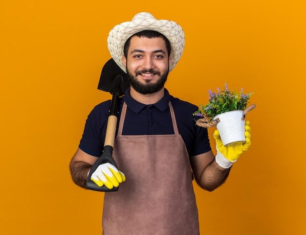 Lächelnder junger kaukasischer männlicher gärtner mit gartenhut und handschuhen, der spaten auf der schulter und blumentopf isoliert auf oranger wand mit kopierraum hält