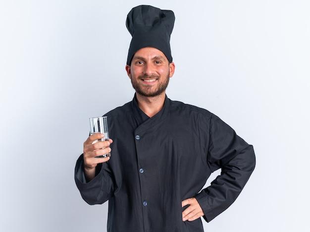 Lächelnder junger kaukasischer männlicher koch in kochuniform und mütze, der die hand auf der taille hält und ein glas wasser hält und die kamera isoliert auf weißer wand betrachtet
