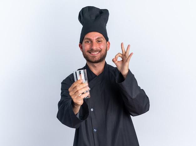 Lächelnder junger kaukasischer männlicher koch in kochuniform und mütze, der ein glas wasser in richtung kamera ausstreckt und auf die kamera schaut, die das ok-zeichen isoliert auf weißer wand mit kopierraum betrachtet