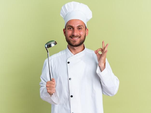 Lächelnder junger kaukasischer männlicher koch in kochuniform und mütze mit schöpfkelle, die in die kamera schaut und das zeichen auf olivgrüner wand isoliert tut