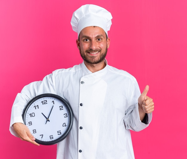 Lächelnder junger kaukasischer männlicher koch in kochuniform und mütze mit uhr mit blick auf die kamera mit daumen nach oben isoliert auf rosa wand