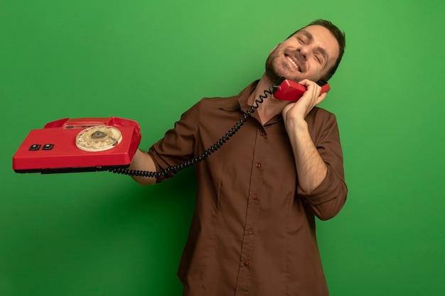 Lächelnder junger kaukasischer mann, der altes telefon hält, das am telefon mit geschlossenen augen spricht, lokalisiert auf grünem hintergrund mit kopienraum