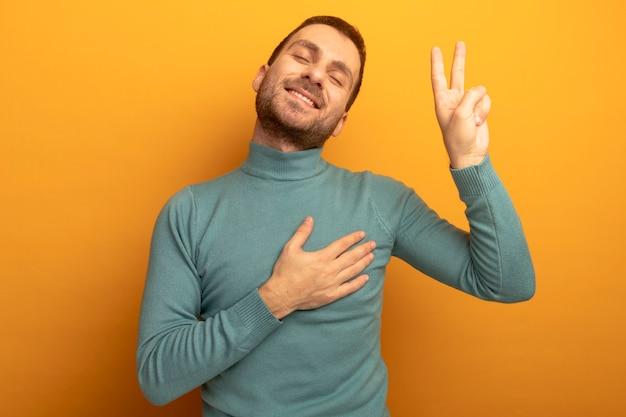 Lächelnder junger kaukasischer mann, der friedenszeichen tut, das hand auf brust mit geschlossenen augen lokalisiert auf orange wand mit kopienraum setzt
