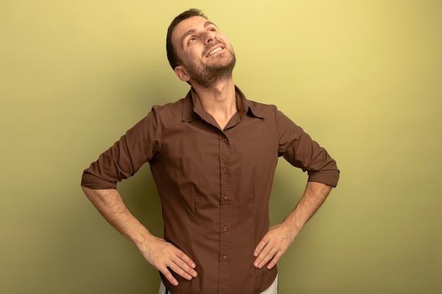 Lächelnder junger kaukasischer mann, der hände auf taille hält, die lokalisiert auf olivgrünem hintergrund mit kopienraum nach oben schaut