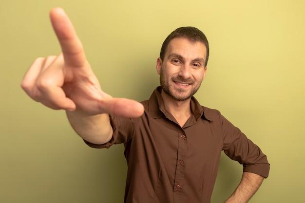 Lächelnder junger kaukasischer mann, der hand auf taille hält und kamera betrachtet, die hand ausstreckt, die verlierergeste tut, lokalisiert auf olivgrünem hintergrund