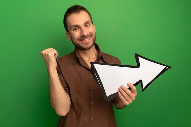 Lächelnder junger kaukasischer mann, der kamera betrachtet, die hinten zeigt und pfeilmarkierung hält, die zur seite zeigt, die auf grünem hintergrund mit kopienraum lokalisiert wird