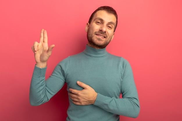 Lächelnder junger kaukasischer mann, der kamera betrachtet, die pistolengeste tut, die hand auf brust lokalisiert auf purpurrotem hintergrund mit kopienraum hält